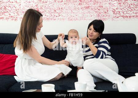 Reife Frau und Tochter spielen mit Baby Girl auf sofa - Stockfoto