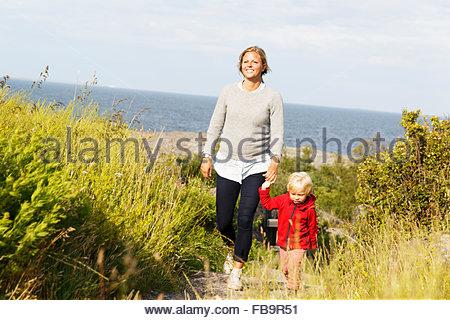Schweden, Stockholmer Schären, Sodermanland, Oja, Frau zu Fuß mit Sohn (2-3) auf Weg durch grünen Rasen - Stockfoto