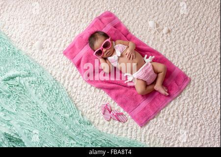 Neugeborenes Babymädchen trägt einen Bikini und Sonnenbrille - Stockfoto
