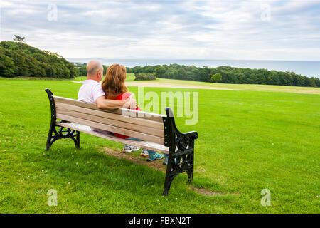 Rückansicht des mittleren Alters paar sitzt auf einer Bank mit Blick auf das Meer - Stockfoto