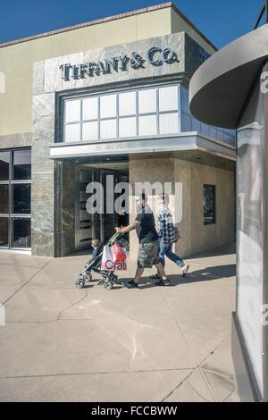 paar treibt junge im Kinderwagen vorbei Reich Marmor verkleidet Eingangsfassade der Tiffany & Co. in eleganten Mini - Stockfoto