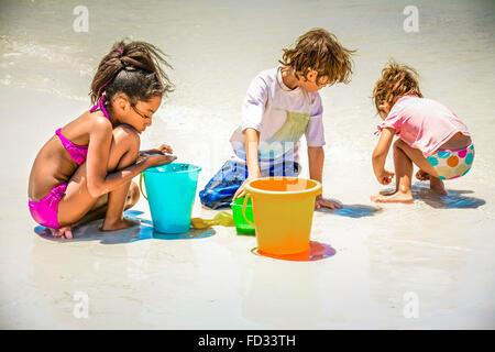 Ein afroamerikanische Mädchen im Bikini und kaukasischen Kinder spielen mit Eimern in den weißen Sand und Surfen - Stockfoto