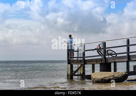 Ein Jugend-Fischen mit einer Angelrute am Ende ein Kai über den Ozean - Stockfoto