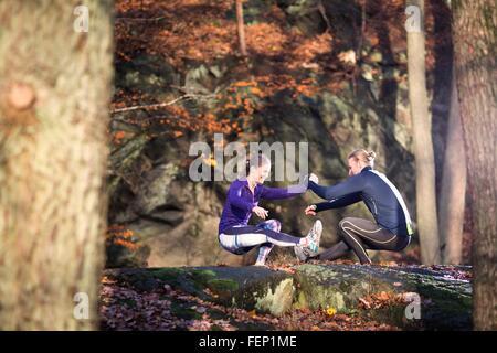 Seitenansicht des Paares auf Felsen im Wald von Angesicht zu Angesicht, Hand in Hand, hocken, balancieren auf einem - Stockfoto