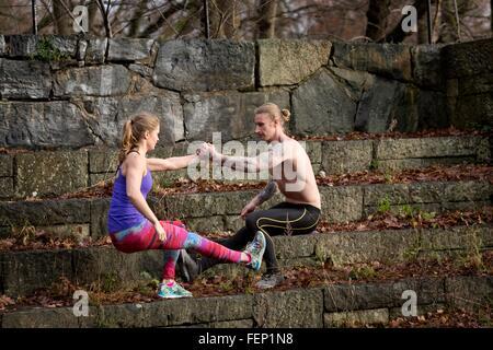 Seitenansicht des paar hocken auf steinernen Stufen, von Angesicht zu Angesicht Händchenhalten balancieren auf einem - Stockfoto