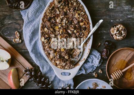 Gebackenes Haferflocken mit Datteln, Äpfel, Bananen und Walnuss ist frisch aus dem Ofen. Ein Löffel serviert und - Stockfoto