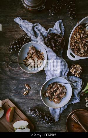 Gebackenes Haferflocken mit Datteln, Äpfel, Bananen und Walnuss ist frisch aus dem Ofen. Ein Teil davon gibt es - Stockfoto