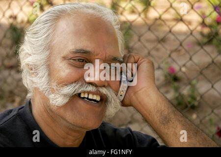 Älterer Herr telefonieren mit Handy im Garten Herr #671 - Stockfoto