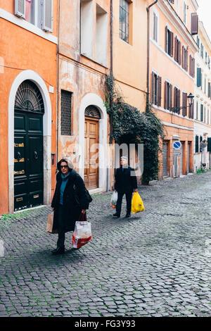 Ein paar trägt Einkäufe nach Hause aus dem Bauernmarkt in Rom, Italien - Stockfoto