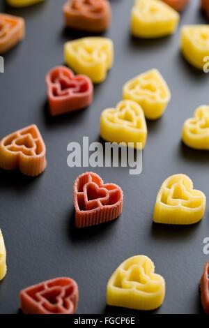 herzförmige Nudeln auf schwarzem Hintergrund - Stockfoto