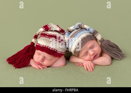 3 Wochen alt eineiige Zwillinge schlafen auf einem grünen Hintergrund - Stockfoto