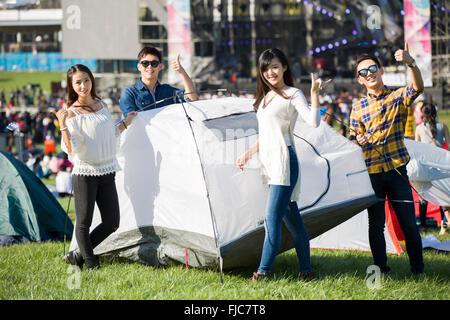 Chinesische Freunde, die ein Zelt auf dem Rasen - Stockfoto