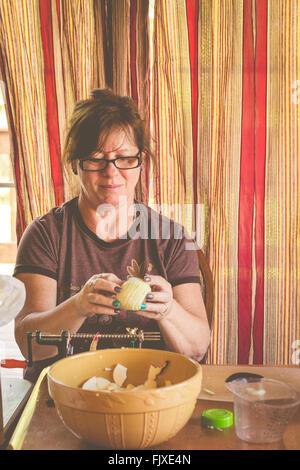 Frau mit Apple zu Hause auf Stuhl sitzend - Stockfoto