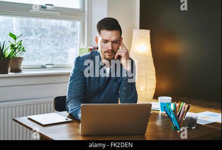 Junger Mann besorgt Unternehmer arbeiten am Schreibtisch auf Laptop ernst - Stockfoto