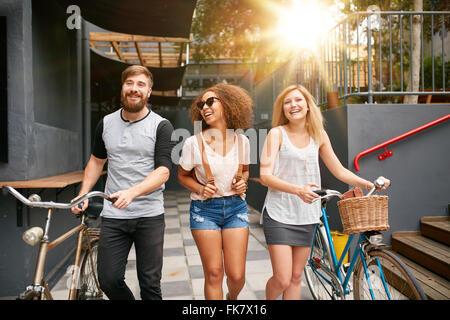 Drei junge Erwachsene gehen gemeinsam Spass haben. Jugendliche mit Fahrrädern zu Fuß im Freien, in der Stadt. - Stockfoto