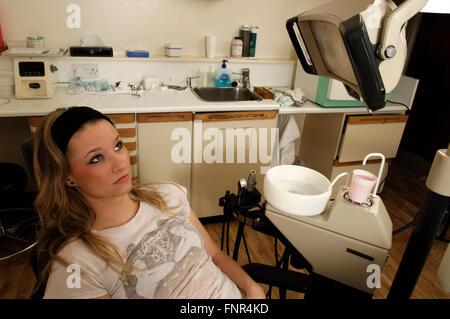 Ein junges Mädchen sitzt auf einem Zahnarztstuhl dabei, ihre regelmäßigen zahnärztlichen Kontrolle. - Stockfoto