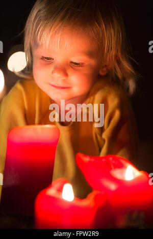 Kleinkind betrachten Advent Kerzen zur Weihnachtszeit - Stockfoto