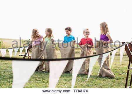 Kinder standen Schlange, um ein Kartoffel-Sack-Rennen starten. - Stockfoto