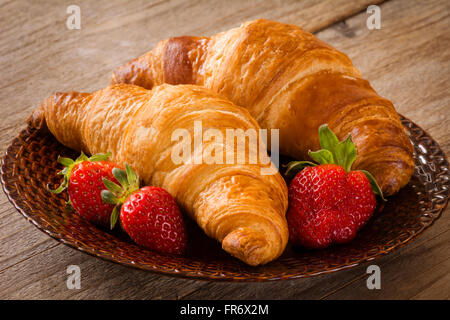 Frische Croissants mit Erdbeeren auf Teller auf hölzernen Hintergrund. Kontinentales Frühstück Essen, Warmton - Stockfoto