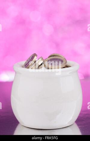 Weißen Keramiktopf mit Münzen auf rosa Hintergrund - Stockfoto