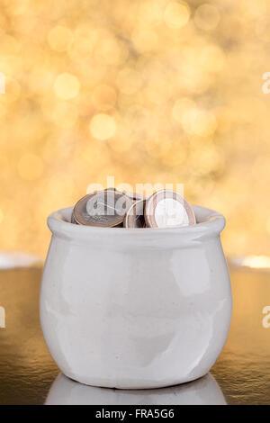 Weißen Keramiktopf mit Münzen auf goldenem Hintergrund - Stockfoto