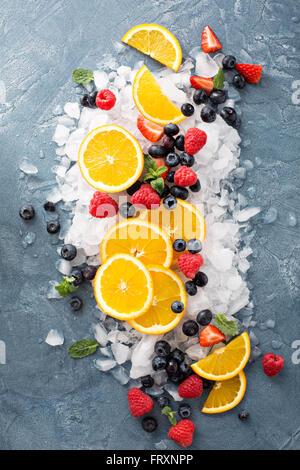 Orangen und Beeren auf Eis - Stockfoto