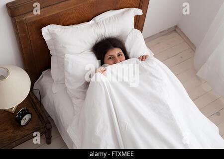 Teenager-Mädchen versteckt unter der Bettdecke im Bett - Stockfoto