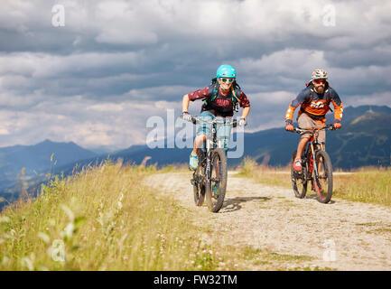Zwei Mountainbiker mit Helmen fahren auf Schotterstraßen, Mutterer Alm in der Nähe von Innsbruck, Patscherkofel, - Stockfoto