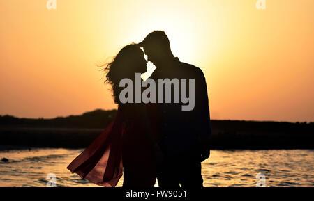 Silhouette paar romancing am Strand bei Sonnenuntergang - Stockfoto