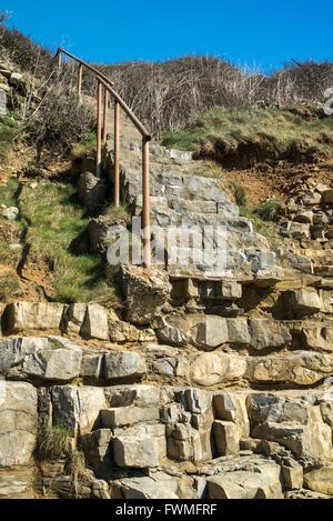 Küstenerosion verlässt die Schritte gestrandet auf halbem Weg die Klippe. - Stockfoto
