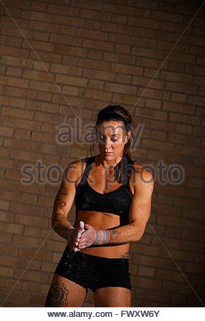Schweden, Frau Abstauben Hände mit Kreide in Turnhalle - Stockfoto
