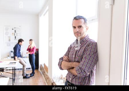 Reifer Mann gelehnt Fenster verschränkten Armen Blick auf die Kamera zu Lächeln - Stockfoto