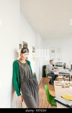 Reife Frau im Büro, Blick auf die Kamera zu Lächeln Wand gelehnt - Stockfoto