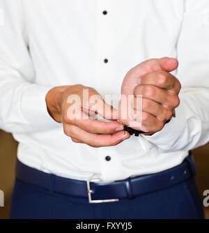 Business Mann Befestigung Knöpfe am Hemd Ärmel zu Hause Nahaufnahme - Stockfoto