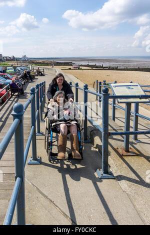 Eine ältere Dame wird hochgeschoben eine Betonrampe in einem Rollstuhl durch ihre Pfleger oder Assistent an einem - Stockfoto