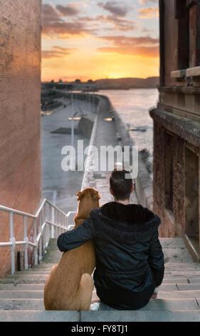 Spanien, Gijon, Rückansicht der Mann und sein Hund sitzt auf der Treppe, Sonnenuntergang - Stockfoto
