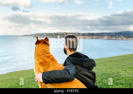 Spanien, Gijon, Rückansicht eines Mannes sitzen auf einer Wiese mit seinem Hund man Entfernung - Stockfoto