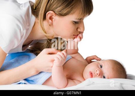 glückliche Mutter ihr kleines Kind Hand küssen - Stockfoto