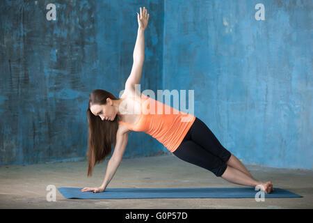 Schöne junge Frau in hellen Kern Übung drinnen Sportswear gekleidet. Yogi-Mädchen Training im Grunge-Interieur - Stockfoto