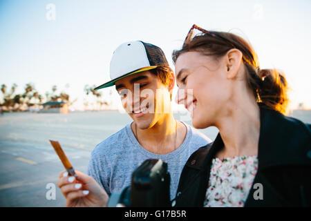 Junges Paar Blick auf sofortige Foto an Küste, Venice Beach, Kalifornien, USA - Stockfoto