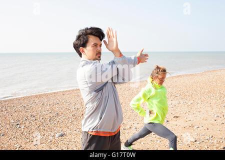 Mann und Frau, training, stretching am Strand von Brighton - Stockfoto