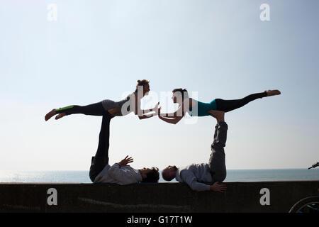 Symmetrische Silhouette Männer und Frauen üben akrobatische Yoga an Wand am Brighton beach - Stockfoto