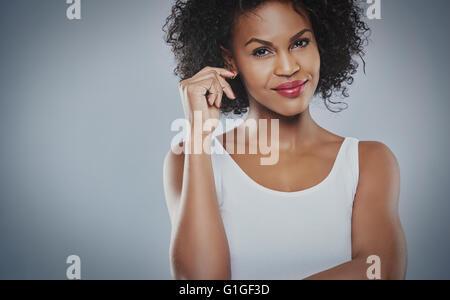 Schöne fröhliche Frau tragen ärmelloses Shirt und verschränkten Armen grinsend über grauen Hintergrund - Stockfoto