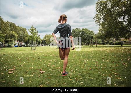 Eine junge Frau ist stretching und Training im park - Stockfoto