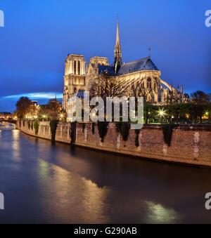 Paris, Frankreich: Kathedrale Notre-Dame in der Abenddämmerung mit Seineufer im Vordergrund - Stockfoto