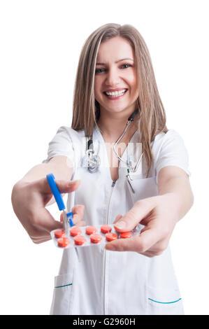 Attraktive Apothekerin schneiden Blister von Pillen mit einer Schere oder Clippers auf weißem Hintergrund - Stockfoto