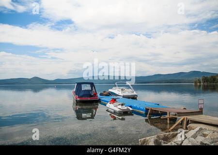 Motorboote sind auf Dock am See. blauer Himmel, Berge und Wald - Stockfoto