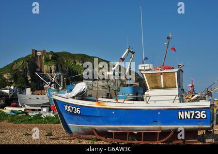 Strand von Hastings, East Sussex, UK im Sommer, mit Fischerbooten und Osthügel - Stockfoto