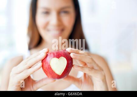 -MODELL VERÖFFENTLICHT. Junge Frau hält einen Apfel mit einer Herzform. - Stockfoto