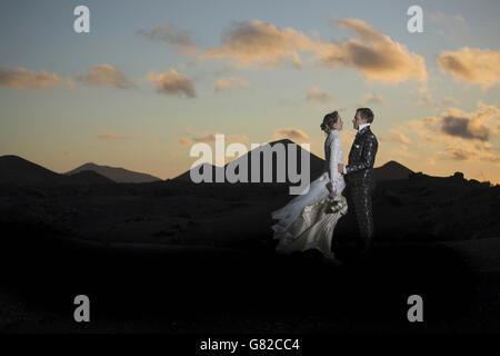 Voller Länge Seitenansicht der romantische Braut und Bräutigam stehen auf vulkanische Landschaft bei Sonnenuntergang - Stockfoto